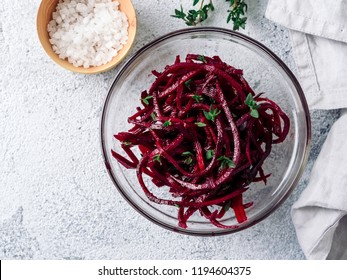 Raw beetroot noodles salad. Vegetable noodles - beet spaghetti on gray cement background. Copy space for text. Ideas and recipe for Clean eating, raw vegetarian food concept. Top view or flat lay.