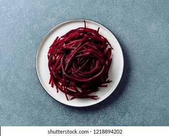 Raw beetroot noodles top view. Vegetable noodles - beet spaghetti on plate over stone background. Clean eating, raw vegetarian food concept.