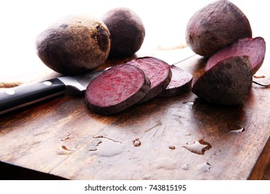raw beetroot on a cutting board on wooden background.