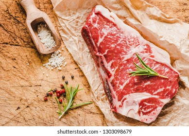 Raw black Angus meat steak on wooden board copy space.