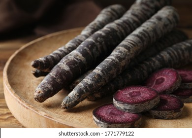 Raw black carrots on wooden plate, closeup