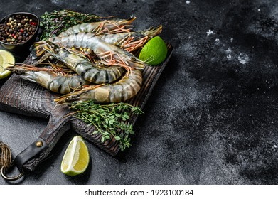 Raw black tiger prawns, shrimps and spices. Black background. Top view. Copy space