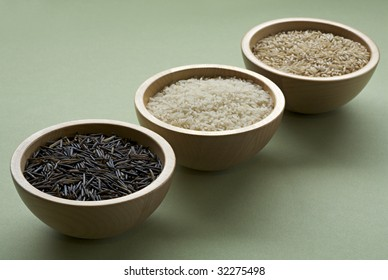 Raw black, white, and brown rice in wooden bowls