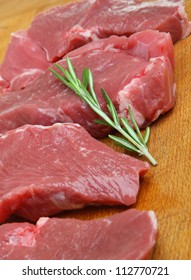 Raw boneless lamb meat steaks on wooden chopping board.