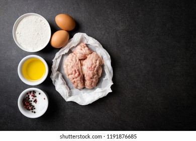 Raw brains and ingredients for cooking fried brains on a stone dark table. Calf or beef brains. Gourmet food. Top view, copy space