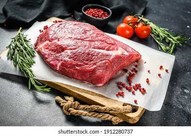 Raw brisket beef cut on a wooden cutting board. Black Angus beef. Black background. Top view