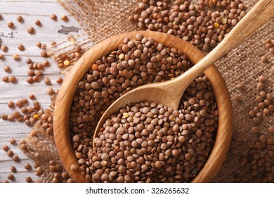 Raw brown lentils in a wooden bowl on the table close-up. horizontal view from above, rustic