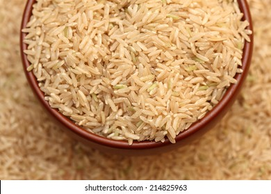 Raw brown rice in a bowl. Selective focus. Closeup.