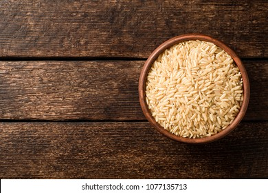 Raw brown rice in ceramic bowl on dark rustic wooden background. Top view. Copy space.