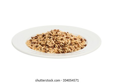 Raw brown rice on porcelain plate isolated on white