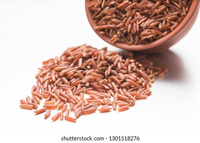 Raw brown rice scattered out of an earthenware cup on a white background.
