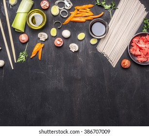 raw buckwheat noodles, pickled ginger, onion, chopped pepper, chopsticks, soy sauce, ingredients for cooking Asian food border ,place for text  on wooden rustic background top view close up