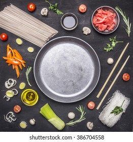 raw buckwheat noodles with vegetables, ginger, chopsticks and ingredients, laid out around the pan place for text,frame on wooden rustic background top view close up