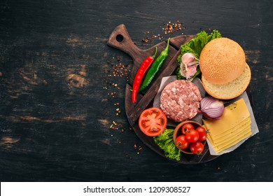 Raw burger Cooking a burger with meat. On a black wooden background. Top view. Free copy space.