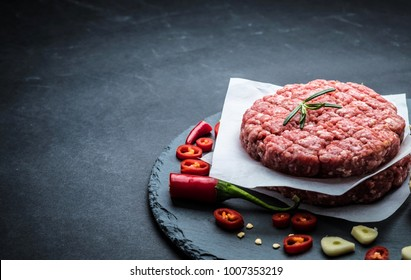 Raw burger cutlet from beef meat with garlic and rosemary on black background with copy space