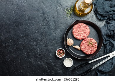 raw burgers - cutlets from organic beef meat with garlic and rosemary in a frying pan on black background, top view with copy space