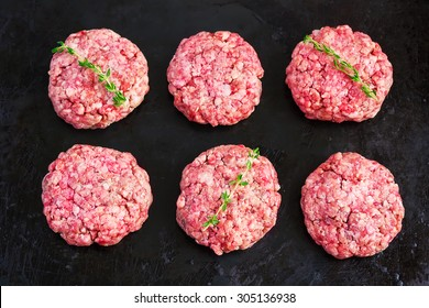 raw burgers from organic beef on black background, top view