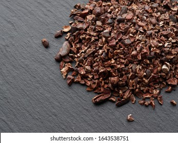 Raw Cacao nibs. Dark background with copy space. Top view.