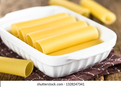 Raw cannelloni pasta in baking dish (Very Shallow Depth of Field, Focus on the left front edge of the first cannelloni in the dish)