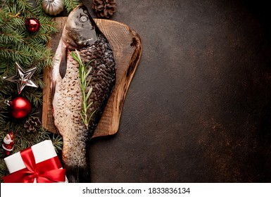 raw carp for preparation for the holiday Christmas on a background of stone with Christmas trees and Christmas decorations  				with copy space for your text