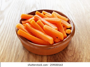 Raw carrot sticks in brown rustic bowl on wooden table