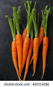 Raw carrots on black background. Food top view