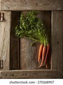 Raw carrots on wood