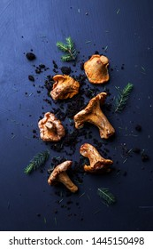 Raw chanterelle mushrooms, soil and pine branches on dark blue background. Moody composition captured from above (top view, flat lay). Free copy (text) space.