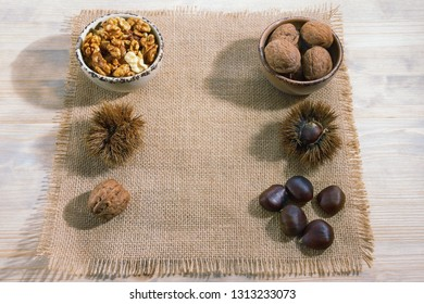 Raw chestnuts in shells, roasted chestnuts, whole walnuts and walnut kernels in a small bowl on a rustic background