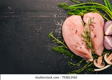 Raw chicken breast fillet with rosemary and spices on a black wooden background. Top view. Free space for text.