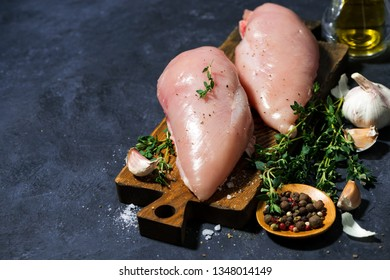 raw chicken breast and fresh thyme on a cutting board, top view horizontal