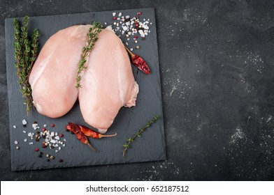 Raw chicken breast for grilled, spices, herbs on dark background, top view. Raw meat chicken for cooking. Delicious balanced food concept. Copy space