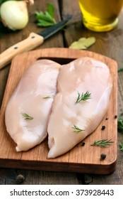 Raw chicken breast on a cutting board