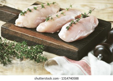 Raw chicken breast on a wooden board. The composition is supplemented with green thyme and a cloth napkin. Processing photos in vintage style. Light wooden background. Close-up. Macro shooting.