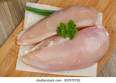 Raw chicken breast with parsley leaves on the wood background