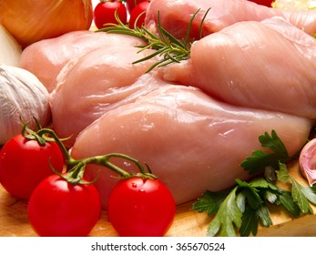 Raw chicken breasts with vegetables on cutting board