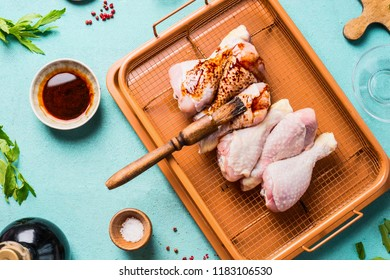 Raw chicken drumsticks with marinate and rub brush on blue background, top view.