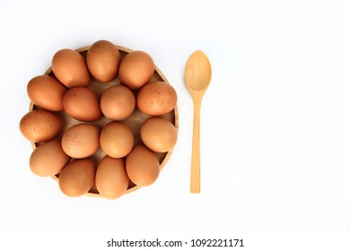 Raw chicken egg withe wooden spoon close-up top view isolated on white background