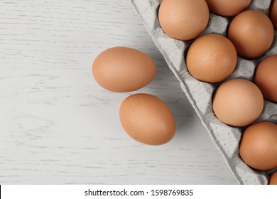 Raw chicken eggs on white wooden table, flat lay