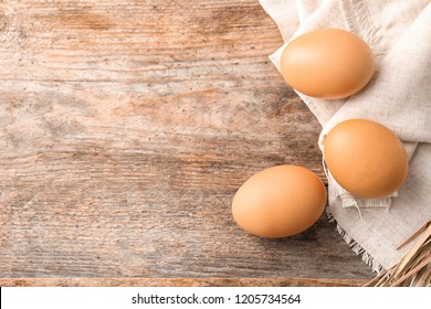 Raw chicken eggs on wooden background, top view. Space for text