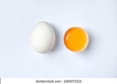 Raw chicken eggs with yolk on white background, top view