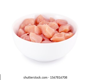 Raw chicken fillet in bowl isolated on white background with clipping path. Small pieces of raw meat on white backdrop.
