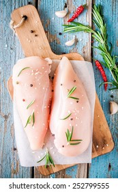 raw chicken fillet with garlic, pepper and rosemary on a blue wooden background