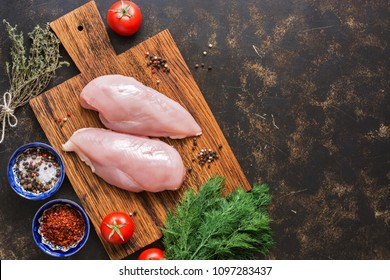 Raw chicken fillet on a cutting board with spices on a dark background. Top view, copy space, flat lay