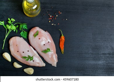 Raw Chicken fillet with spices on a black background.