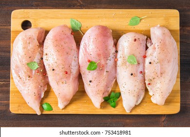 Raw chicken. Chicken fillets on a cutting board against the background of a wooden table. Meat chicken ingredients for cooking. Flat lay. Top view. Chiken food.
