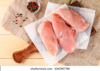 raw chicken fillets on wooden cutting board