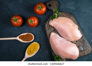 Raw chicken fillets on wooden cutting board with spices in spoons, tomatoes and mushrooms, top view