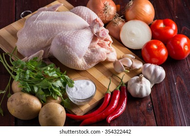 Raw chicken and fresh vegetables on wooden background
