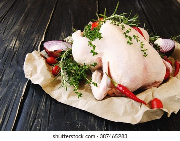 raw chicken with herbs spices ingredients, ready for cooking, on a wooden table, selective focus